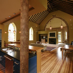 The kitchen opens to the living and dining area in the full height sanctuary space with original floors restored and ceiling beams exposed.