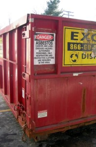 The triple bagged asbestos is placed in a sealed and locked dumpster.